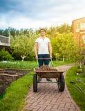 Tragende Schubkarre des Mannes am schönen Garten Lizenzfreie Stockfotos
