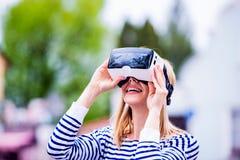 Tragende Schutzbrillen der virtuellen Realität der Frau in der Straße Lizenzfreies Stockbild