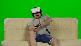 Tragende Schutzbrillen der virtuellen Realität des Mannes Atelieraufnahme, weiße Couch Grüner Bildschirm stock footage