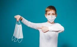 Tragende Schutzmaske des Jungen, die auf Masken zeigt Lizenzfreies Stockbild