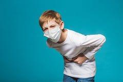 Tragende Schutzmaske des Jungen, die Magenschmerzen hat Stockbilder