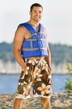 Tragende Schwimmweste des Mannes am Strand Stockfotos