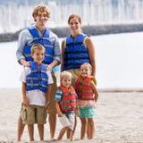 Tragende Schwimmwesten der Familie am Strand Lizenzfreie Stockbilder