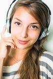 Tragende silberne Kopfhörer des schönen Brunette. Stockfotografie