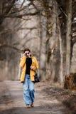 Tragende Sonnenbrille der Frau und ein gelber Mantel lizenzfreie stockfotografie