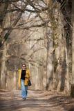 Tragende Sonnenbrille der Frau und ein gelber Mantel stockbilder