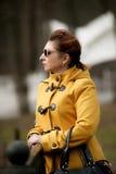 Tragende Sonnenbrille der Frau und ein gelber Mantel stockfotos
