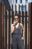 Tragende Sonnenbrille der hübschen jungen stilvollen Frau, die gegen einen Zaun steht stockbilder