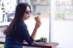 Tragende Sonnenbrille der jungen attraktiven Frau, die Tasse Kaffee hält Stockfoto
