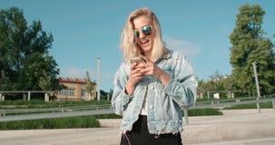 Tragende Sonnenbrille der jungen Blondine unter Verwendung des Telefons während des sonnigen Tages in einer Stadt Stockfotos