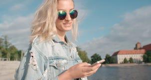 Tragende Sonnenbrille der jungen Blondine unter Verwendung des Telefons während des sonnigen Tages in einer Stadt Lizenzfreie Stockfotografie