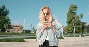 Tragende Sonnenbrille der jungen Blondine unter Verwendung des Telefons während des sonnigen Tages in einer Stadt Lizenzfreie Stockbilder