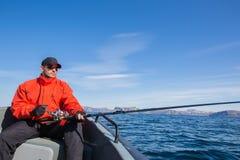 Tragende Sonnenbrille des Fischerathleten mit einer spinnenden Stange in seinem Lizenzfreie Stockbilder