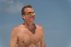 Tragende Sonnenbrille des hemdlosen Mannes am Strand. Stockfoto
