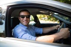 Tragende Sonnenbrille des jungen Mannes beim Fahren des Autos Stockfoto