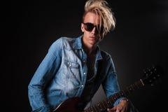 Tragende Sonnenbrille des kühlen jungen Gitarristen Stockfoto