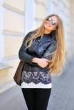 Mode-Modell in der Sonnenbrille mit der Tasche, die draußen lächelt Lizenzfreies Stockfoto