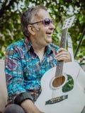 Tragende Sonnenbrille Hippie-Sankt mit einer Gitarre stockbild