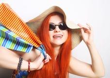tragende Sonnenbrille und Hut der redhair Einkaufsfrau Stockfoto