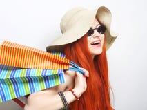 tragende Sonnenbrille und Hut der redhair Einkaufsfrau Stockbild