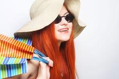 tragende Sonnenbrille und Hut der redhair Einkaufsfrau Stockfotografie