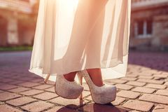 Tragende Stöckelschuhe und Weiß der stilvollen Frau kleidet draußen an Schönheitsmode stockfotografie