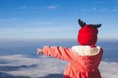 Tragende Strickjacke des netten asiatischen Kindermädchens und warmer Hut ihren Arm und das Zeigen auf schöne Natur im Winter vor lizenzfreies stockbild