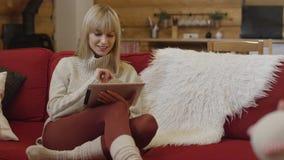 Tragende Strickjacke des schönen Mädchens unter Verwendung einer Tablette zu Hause Lizenzfreie Stockbilder