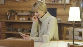 Tragende Strickjacke des schönen Mädchens unter Verwendung einer Tablette zu Hause Lizenzfreies Stockfoto