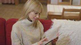 Tragende Strickjacke des schönen Mädchens unter Verwendung einer Tablette zu Hause Lizenzfreie Stockfotografie