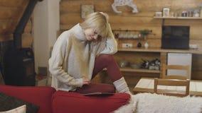 Tragende Strickjacke des schönen Mädchens unter Verwendung einer Tablette zu Hause Stockfoto