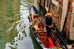 Tragende Strohhutst?nde des attraktiven jungen italienischen Gondolieren in der traditionellen Gondel mit Luxusdekor lizenzfreie stockfotos