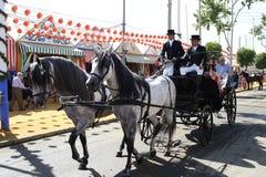Tragende Touristen des Pferdewagens an der Sevilla-Messe Stockbild