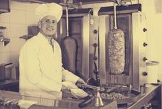 Tragende Uniform des reifen Mannkochs, die Kebab vorbereitet Lizenzfreie Stockfotografie