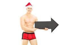 Tragende Unterhosen des nackten Kerls und Weihnachtshut, der einen Pfeil hält Lizenzfreies Stockfoto