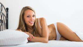 tragende Unterwäsche der Frau, die auf Bett aufwirft Stockfotografie