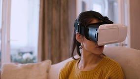 Tragende VR-Kopfhörergläser der jungen Frau virtuelle Realität zu Hause, sitzend auf Sofa stock video footage