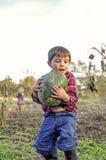 Tragende Wassermelone des Jungen im Flecken lizenzfreie stockfotos