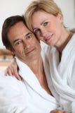Tragende weiße Bademäntel der Paare Stockfotografie
