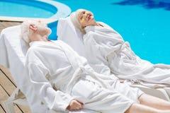 Tragende weiße Bademäntel des Mannes und der Frau im Ruhestand, die nahe Pool kühlen Stockfotografie