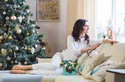 Tragende weiße gestrickte Strickjacke der jungen schönen brunette Frau zu Hause am Fenster stockfotos