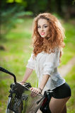 Tragende weiße Spitzebluse des schönen Mädchens und schwarze kurze Hosen, die Spaß im Park mit Fahrrad haben Recht rote Haar Lizenzfreie Stockfotografie