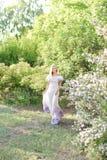 Tragende weiße Stellung der jungen Frau Kleidernahe weißen lila Blumen stockfotografie