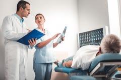 Tragende weiße Uniform dunkelhaarigen Doktors, die auf Empfehlungen hört lizenzfreie stockfotografie
