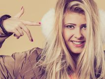 Tragende Winterpelzohrenschützer der Frau, die auf sie zeigen Lizenzfreies Stockfoto