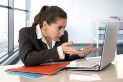 Tragender Anzug der Geschäftsfrau, der an Laptop-Computer am modernen Büroraum arbeitet stockfotos