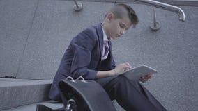 Tragender Anzug des kleinen Jungen, der auf der Treppe auf der Straße schreibt auf der Tablette sitzt Kind als Erwachsener stock video footage