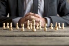 Tragender Anzug des Mannes, der vor weißem Schach sitzt Lizenzfreies Stockfoto