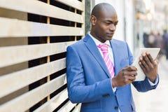Tragender Anzug des schwarzen Mannes, der seinen Tablet-Computer betrachtet Stockfotografie