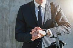 Tragender Anzug des stilvollen Mannes betrachtet Uhr Stockfotos